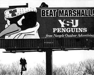 12/18/91 - Doug Oster.Go YSU: A billboard being erected at Martin Luther King Blvd. and the Madison Ave. freeway by Steve Savick of Niles, left, and Harmon Wolfe of Liberty both who work for Naegle Sign Company. The picture was shot from Rayen Ave. in Youngstown.