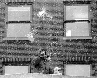 01/17/91 - Doug Oster.YSU PARADE: Kenneth Richards of Youngstown who works as a heating and air conditioning supervisor for Ohio One Corp. throws confetti off the roof of the Ohio One Building.