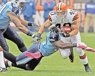 Cleveland Browns running back Peyton Hillis runs through a tackle by Tennessee Titans outside linebacker Akeem Ayers (56) as defensive end Derrick Morgan, left, moves in in the first quarter of an NFL football game Sunday, Oct. 2, 2011, in Cleveland. (AP Photo/Mark Duncan)
