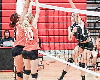 Girard player Bryanna Jay, 19, hits the ball as Springfield's senior Brooke Schrieber, left, and sophomore Morgan Buchenic go up for the block. Girard rallied to win to the volleyball match.