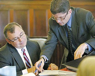 Marion H. Little Jr., left, lawyer for The Vindicator and 21 WFMJ-TV, examines court documents with Anthony Cillo, an assistant Lorain County prosecutor and a special prosecutor in the dismissed Oakhill Renaissance Place criminal conspiracy case.