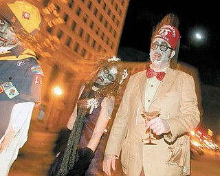 Dressed as zombies, Aidan, 10, Bailey, 13, and their father, John Hughes, of Niles, roamed Federal Plaza as part of the Zombie Crawl last year in downtown Youngstown.