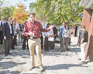 Youngstown Neighborhood Development Corp. deputy director Ian J. Beniston discusses urban agriculture and development at an urban farm on Youngstown's South Side. The tour was part of the Ohio CDC Association's annual conference.