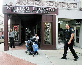 Lisa Reali, owner of William Leonard's barber and beauty shop, waves at patrolman Michael Cox as he walks his downtown beat. The Youngstown Police Department began walking the daytime downtown beat last week.