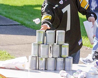 George Froble, 45, of Youngstown knocks over cans during the Harvest Carnival.