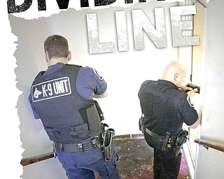 Liberty police officers Ray Buhala, left, and Robert Altier, right, inspect a vacant apartment building in the southern part of the township. As the township evolves from a rural to an urban setting, police are forced to fight a change in the types of crimes with a dwindling police force.