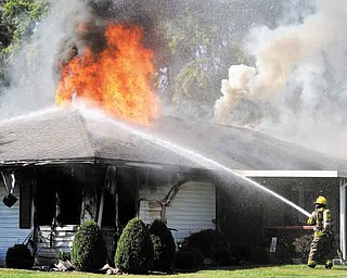 A firefighter from the Chillicothe Fire Department sprays water on a fire which broke out during a standoff with police at a home in Brewer Heights area of Chillicothe, Ohio on Saturday, Oct. 8, 2011. (AP Photo/The Chillicothe Gazette, Heather Cory)