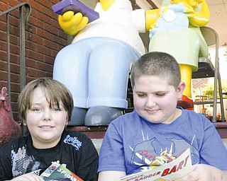 Homer, Marge and Maggie Simpson watch over Solomon Kennedy, 8, of Youngstown, and Jay Dulin, 11, of Austintown, as they look at comic books Saturday during Lawn-Con in the yard of local artist Chris Yambar.