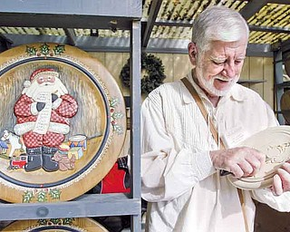Woodcarver Don Lorigan of Kittanning, Pa., works on one of his hand carved and hand painted holiday plates at Christmas in the Woods festival.