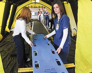 Humility of Mary Health Partners conducted orientation sessions about a decontamination unit for senior leadership in St. Elizabeth Health Centers in Youngstown and Boardman and at St. Joseph Health Center in Warren on Monday. Here St. Elizabeth registered nurses, Brenda Luchs, left, and Amanda Lencyk, demonstrate how nonambulatory patients are moved through a decontamination tent.