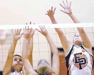 Mineral Ridge's Alyssa Harkins (21) tries to get a shot past East Palestine's Logan Gatchel, left, and Kae Huff during Tuesday's volleyball match at Mineral Ridge.