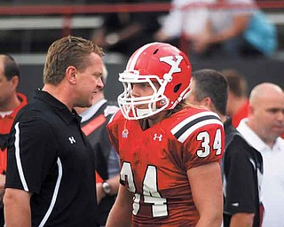 Youngstown State coach Eric Wolford talks to linebacker Thomas Sprague on the sideline during the Penguins' game against Valparaiso on Sept. 10. After losing two straight games, Wolford said he's not going to let his team settle for being average.