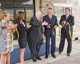 An official ribbon-cutting ceremony for Austintown's new Holiday Inn Express and Suites was Wednesday morning. From left, assistant general manager Heidi Pelfrey, general manager KayLou King and owner Frank Pasqualetti celebrate with Brent Carnaha, of Seven Seventeen Credit Union and Atty. Jeffrey Lutz, who represents Pasqualetti, after cutting the ribbon.