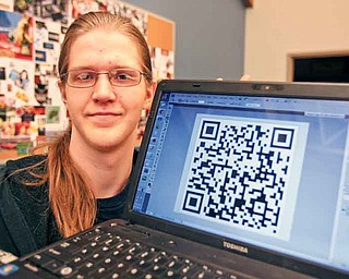 Calvin Neer, a senior from Jackson-Milton, shows off the Quick Response Code that links to a 30-second video ad about Mahoning County Career and Technical Center's culinary arts program. Students in MCCTC's interactive multimedia/visual art and design class completed marketing projects for the school's programs.