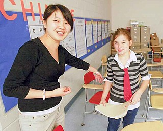 Zhen Zhen Li assists sixth-grader Jenna Kelvert with her work. Over the past five years, Hubbard school district has introduced both Chinese and Spanish to its elementary and middle school curricula.