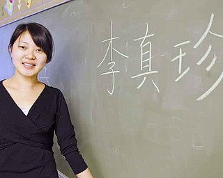 Zhen Zhen Li, a 26-year-old Chinese teacher, stands next to her name spelled out in Chinese. Li will teach 350 students from both the elementary school and the middle school for the next three years as part of a district initiative of teaching foreign languages at a younger age.