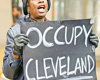 Mae Thompson, 67, protests Wednesday in Cleveland as part of the Occupy Wall Street movement. The demonstration is one of many across the country. An Occupy Youngstown protest will be Saturday in downtown Youngstown. The origins of the movement come from Canada and the Middle East.