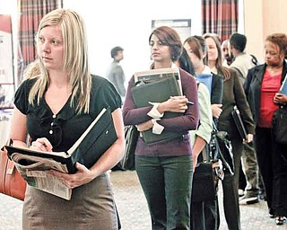 FILE - In this Sept. 14, 2011 file photo, Annelie Ingvarsson, left, waits in line to talk to potential employers during a National Career Fairs job fair, in Bellevue, Wash. The United States added 103,000 jobs in September, an improvement over this summer and just enough to calm fears of a new recession that have hung over Wall Street and the nation for weeks. (AP Photo/Ted S. Warren, File)