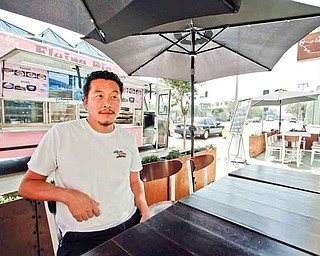 Owner Joe Kim sits at the outside table at the newly opened Flying Pig restaurant in Los Angeles, California, September 2, 2011. The Flying Pig food truck started out as a truck as a way for Kim to test out recipes before launching a restaurant. (Ricardo DeAratanha/Los Angeles Times/MCT)