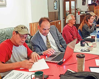 Members of Occupy Youngstown make plans at the Lemon Grove Café for a Saturday rally in downtown Youngstown. They are, from left, Rick Montanez of Lowellville, an unidentified man, Joseph Nestasie of Hillsville, Pa., and Lauren Lenio of Boardman.