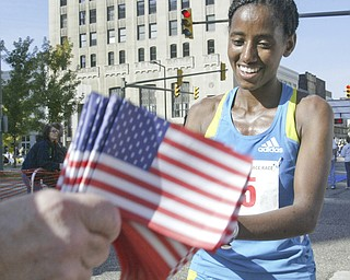 William D. Lewis|The Vindicator  Peace Race Sunday womens 1 rst place runner Mumis Eboka (check spelling). gets flag at end of race.