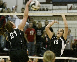 William D. Lewis|The Vindicator Salem's #21 Kathethrine Stiff tips the ball over the net while Canfield's Nicole Luklan defends Thursday at Boardman.