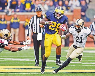 Michigan running back Fitzgerald Toussaint (28), a graduate of Liberty High School, rushes away from Purdue defensive back Taylor Richards (4) and cornerback Ricardo Allen (21) for a touchdown in the third quarter of a game in Ann Arbor, Mich. Michigan won 36-14.