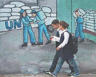 Palestinian schoolgirls walk past graffiti on a wall depicting UN humanitarian-aid supplies in Gaza City on Monday. Palestinians became full members of the U.N. cultural and educational agency Monday, in a highly divisive move that the United States and other opponents say could harm renewed Mideast peace efforts.