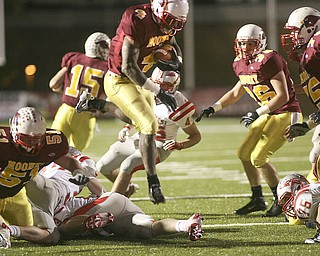 ROBERT  K.  YOSAY  | THE VINDICATOR --..Mooneys #4 Marcus McWilson  jumps over defenders as he takes the ball in for another Mooney Score Cardinal Mooney Cardinals vs Canal Fulton Northwest Indians at Stambaugh Stadium in the Regional Quarterfinals .--30-..(AP Photo/The Vindicator, Robert K. Yosay)