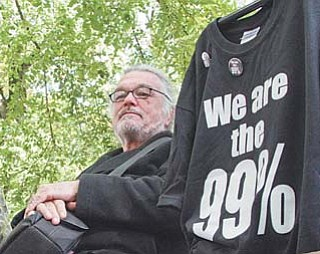 Walter Lichtenberg sits on a park bench selling shirts and buttons at the Occupy Portland camp in downtown Portland, Ore.