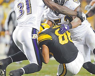 Baltimore Ravens safety Bernard Pollard (31) and LB Ray Lewis (52) hit Pittsburgh Steelers wide receiver Hines Ward after he made a catch in the second quarter of Sunday's NFL game in Pittsburgh. Ward was injured and helped from the fi eld. The Steelers rallied but came up short against the Ravens, losing 23-20.