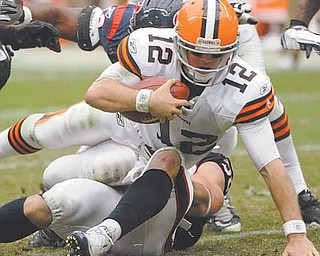Cleveland Browns quarterback Colt McCoy (12) is sacked by a Houston Texans defenders in the third quarter of Sunday's NFL game at Reliant Stadium in Houston. The Browns lost 30-12, with McCoy playing the role of pinata in his fi rst NFL game in his home state, getting sacked four times and unoffi cially hit on eight other occasions.