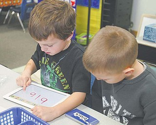 North Jackson kindergartners Tommy Derrow, 5, and Jack Pittman, 6, practice writing words on an iPad. Using a federal grant, the district began implementing the digital tablets into its curriculum this month.