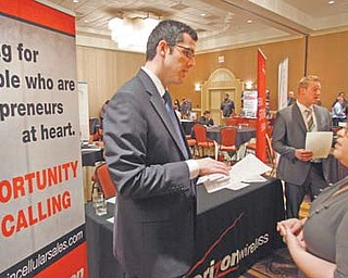 Blake Andrews, left, with Verizon, visits with prospective employees during a job fair in San Antonio. Employers advertised more jobs in September than at any other point in the past three years, a hopeful sign that the job market is slowly improving.