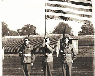 Leo Arnaut, left, and his identical twin brother, William, right, are pictured with a fellow soldier holding the flag. They joined the Army in 1942 and were discharged after both were shot while in the same fox hole during the D-Day invasion in France in 1944. Both received the Purple Heart. They were born and raised in Youngstown. Leo died in February 2010, and William, in March 1995. Leo's daughter, Colleen Joerndt, submitted the picture, adding that their family members are all very proud of them.