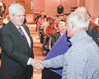 Republican presidential hopeful former House Speaker Newt Gingrich shakes hands with an audience member while campaigning at the Westin Hotel at Detroit Metro Airport in Romulus, Mich., on Thursday.