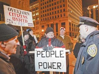 Youngstown police Capt. David McKnight speaks with Occupy Youngstown protesters Thursday night. An order from the police chief was given for the group to remove a tent and barrel from the protest site.