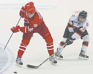 Phantoms defender Jordan Young (5) tries to keep the puck from the Fighting Saints' Max Gardiner during Sunday's game at the Covelli Centre. The Saints won 4-3.