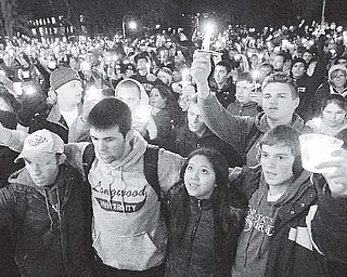 In this photo from Friday, people gather in front of the Old Main building for a candlelight vigil on the Penn State campus in State College, Pa., in support of the reported victims of a child-sex-abuse scandal involving a former assistant coach. As Penn State leaves a harrowing week behind and takes tentative steps toward a new normal, students and alumni wonder what exactly that means.