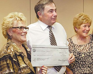 Howard and Mary Kay Hartzell present a $25,000 check to Youngstown State University President Cynthia Anderson, left, during a luncheon on campus. The Hartzells have raised $250,000 for scholarships in honor of their son, Youngstown Police Officer Michael Hartzell, who was killed in the line of duty in 2003. The presentation was Monday.