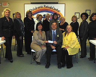 """'Tutor U' gets a boost. Members of the Trumbull County Women's History Celebration Committee recently presented a $500 check to Executive Director Robert C. Foster of the Children's Rehabilitation Center for its """"Tutor U"""" program. The program is designed to assist third-grade through eighth-grade youngsters who need extra academic help. Tutor U is offered from 4 to 7:30 p.m. Monday through Friday at the center, 885 Howland-Wilson Road NE, Howland. Call 330-856-2107, ext. 106, to set up a tutoring appointment. Standing, from left to right, are Julie Vugrinovich, Esther Gartland, Beky Davis, Theresa Salcone, Roz Jackson, Pam Hallett, Judie Hartley, Jo Anne Liptak, Kenya Howard and Stephanie Furano. Seated are Renee Maiorca, Foster and E. Carol Maxwell."""