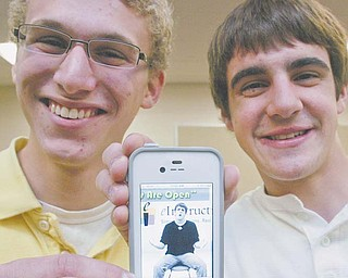 """From left, Girard seniors David Meigs, 18, and Zack Teter, 17, pose with an iPhone that is playing their video """"Our Minds Are Open,"""" a spoof on the Creed song """"With Arms Wide Open."""" The two hope their video, a finalist in the eInstruction Classroom Makeover Contest, will garner enough votes to win their school $75,000 worth of high-tech instructional upgrades."""