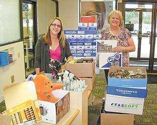 Glasses overflowing: The Boardman Lions Club made a donation of more than 1,400 pairs of used eyeglasses and 150 pairs of sunglasses to LensCrafters in the Boardman Plaza. September's donation was the largest single donation received at the branch. Above, Karen Kannal, right, Boardman Lions Sight Chairwoman, presents the glasses to Kayla Stone, LensCrafters licensed optician. Drop-off locations for eyeglasses include Boardman United Methodist Church, the Spectacle Spot, Boardman Library, St. Luke's Church, Boardman Center Middle School and Sam's Club. Stone says the eyeglasses are sent to Cincinnati for distribution to Mexico, Paraguay and India, among other countries.