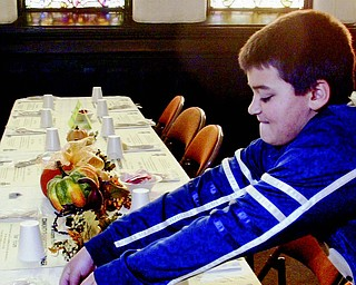 Nick Kacir, 12, a member of Boy Scout Troop 55, sets the table before the Community Thanksgiving Dinner on Thursday at First Presbyterian Church in Youngstown.