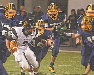 Kirtland defenders swarm Crestview quarterback Adam Coppock during the Division V regional championship game Friday at Mollenkopf Stadium in Warren. The Hornets overwhelmed the Rebels, 35-7.