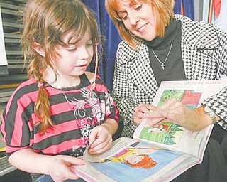 Author Rebecca Macri and Courtney Ross, 7, look over the book that was inspired by the Watson Elementary first-grader.