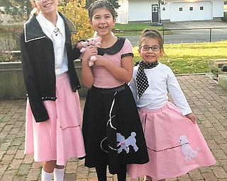 """Ready for the record hop: Sisters D'Ella, Mille and Sophie Heschmeyer of Liberty celebrated the 50th day of school when Akiva Academy in Youngstown had a '50s day. The girls donned their best 1950s outfits for the occasion as students and teachers dressed in poodle skirts, rolled up jeans, slicked-back hair and leather jackets. They even listened to music on what the kids described as """"weird dishes"""" — vinyl LPs. The whole elementary school learned about the culture of the 1950s era and enjoyed pizza and root beer floats for lunch."""