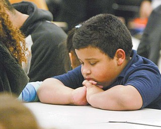 Edwin Rodriguez, a second-grader at Williamson Elementary in Youngstown, gives thanks Monday before a Thanksgiving dinner at the school. Students and their families were treated to the meal after parents attended parent-teacher conferences last week.