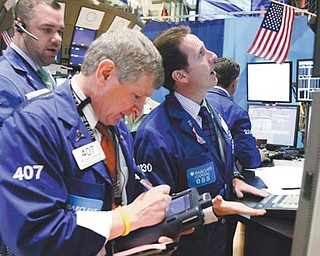 Specialist Glenn Carell, right, works at his post on the floor of the New York Stock Exchange on Monday. The collapse of talks aimed at reducing the staggering U.S. budget deficit weighed on world markets Tuesday.