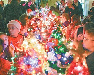 """Fourth-grade students at Springfield Elementary School sang carols Tuesday as they created a """"Christmas Tree Lane"""" with their personalized trees."""